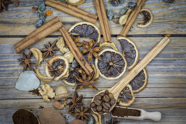 A beautiful arrangement of dried lemons, cinnamon, coffee on wooden spoons on wood