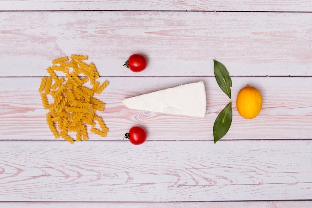 Beautiful arrangement of uncooked fusilli pasta; tomatoes; cheese; bay leaves and lemon on wooden background