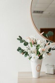 벽 바탕에 꽃병에 아름 다운 인공 꽃