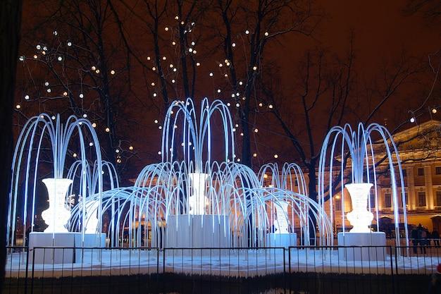 街の冬の夜の照明付きの美しい人工噴水。