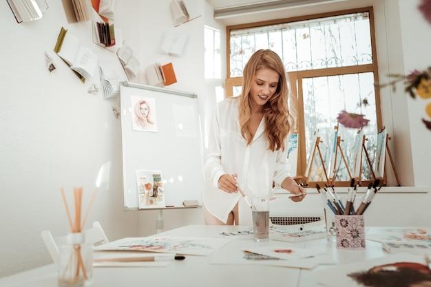 아름다운 예술가. 그녀의 스튜디오에서 단순히 놀라운 일을 느끼는 아름다운 blonde-haired 아티스트