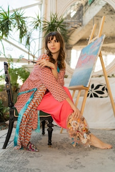 Beautiful artist woman in bohemian outfit posing with brush and palette in her art studio.