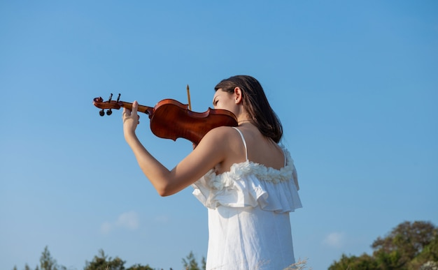 Beautiful asia girl white dress playing on a violin
