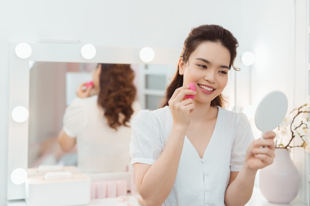 아름다운 아시아 여성은 메이크업 스펀지, 프레스드 파우더를 사용하여 주름, 잡티, 모공을 감추기 위해 아름다운 얼굴에 적용하거나 메이크업을 적용하여 매끄러운 피부 얼굴을 만듭니다. 여자들은 거울을 본다. 복사 공간