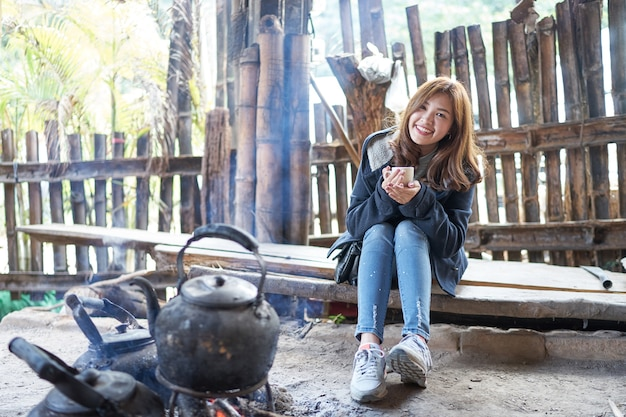 Beautiful asia woman holding coffee cup and sitting on wood near kettle on fire.