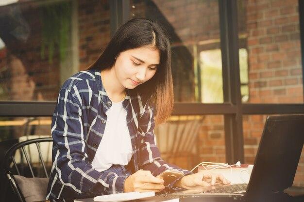 美しいアジアの女性は、コンピュータと携帯電話を使用して幸せに働く