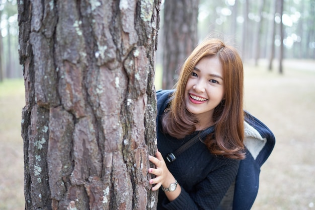 Beautiful asia woman with brown hair hiding behind pine tree