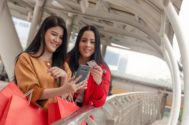 携帯電話、クレジットカード、買い物袋を保持している美しいアジアと白人の若い女性