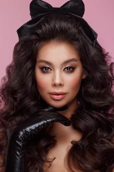 볼륨 컬, 클래식 메이크업 및 섹시한 입술을 가진 아름다운 아시아 갈색 머리 모델