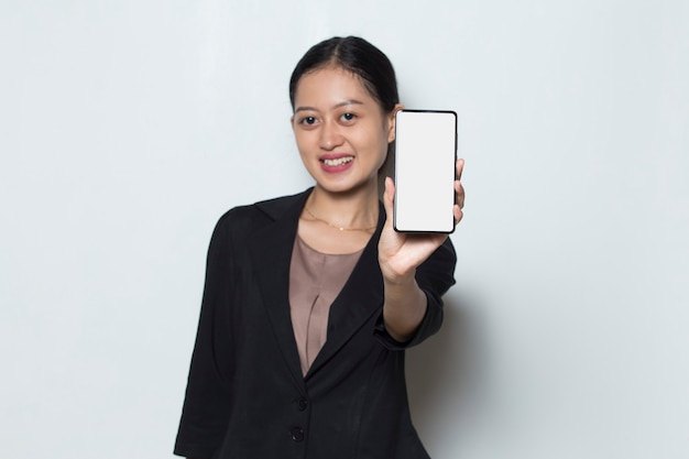 Beautiful asian business woman demonstrating mobile cell phone