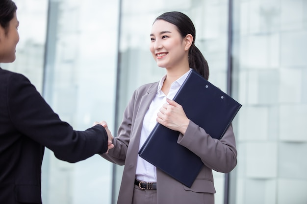 현대 도시 작업 사무실에서 악수 아름 다운 아시아 비즈니스 여자.