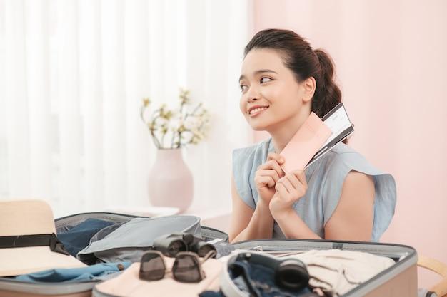 休日の週末の旅行旅行者のための旅行を準備するために黄色のスーツケースとパスポートとチケットを持って笑っている美しいアジアのビジネス女性。