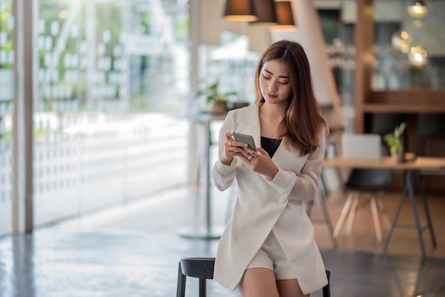 現代のオフィスでスマートフォンを使用して立っている美しいアジアのビジネス女性。