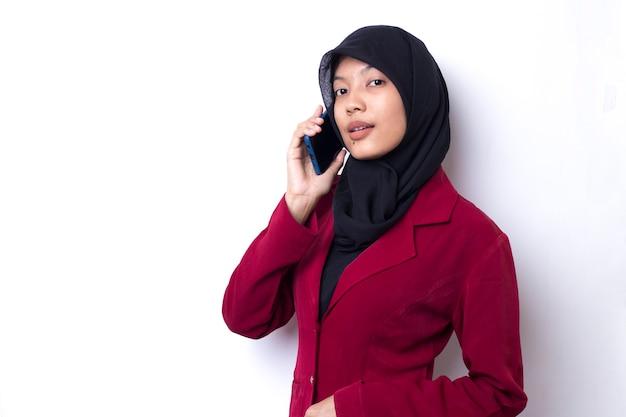 Красивая азиатская бизнес-леди с портретом хиджаба с помощью телефона на белом пространстве