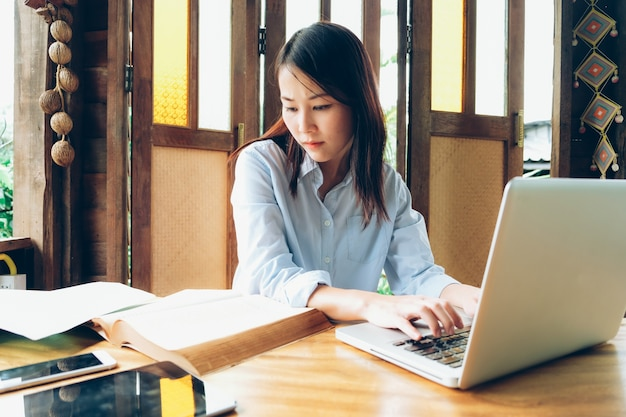 Beautiful asian business woman working with laptop, mobile phone, and tablet.