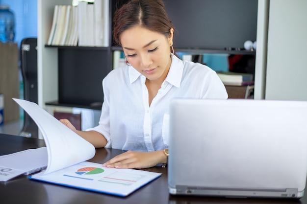 아름 다운 아시아 비즈니스 여성 문서를 확인하고 집에서 일하기 위해 노트북을 사용