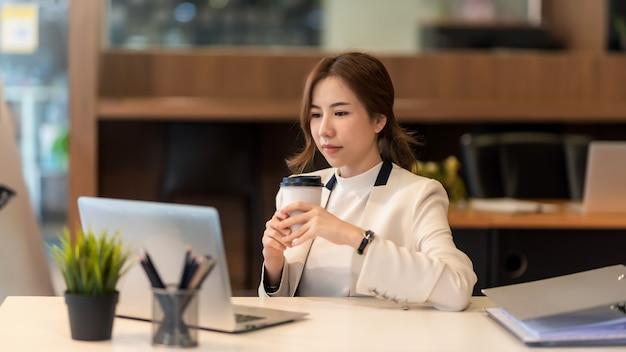 사무실에서 커피잔을 들고 있는 아름다운 아시아 사업가