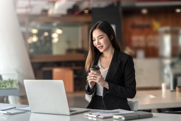 Красивая азиатская коммерсантка, держащая кофе, смотрящий на компьтер-книжку в офисе.