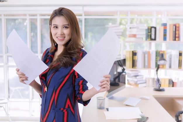 집에서 일하는 동안 종이 문서를 들고 있는 아름다운 아시아 여성.