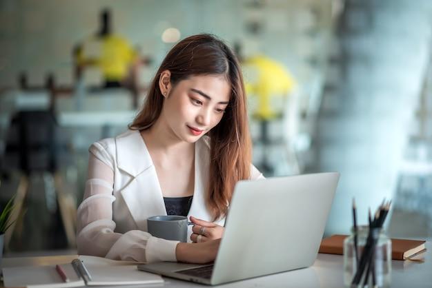 Красивая азиатская бизнес-леди или финансовый менеджер, работающий в современном офисе на ноутбуке