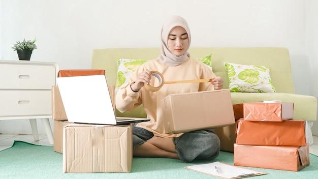 Красивая азиатская бизнес-леди, упаковка заказов клиентов в своей комнате