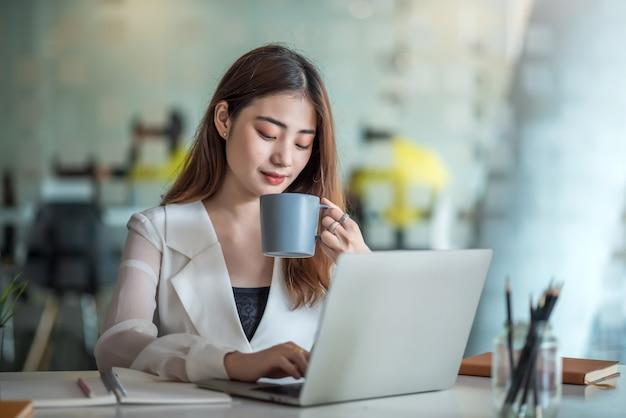 Красивая азиатская деловая женщина сидит, пьет кофе и счастливо работает с ноутбуком в офисе