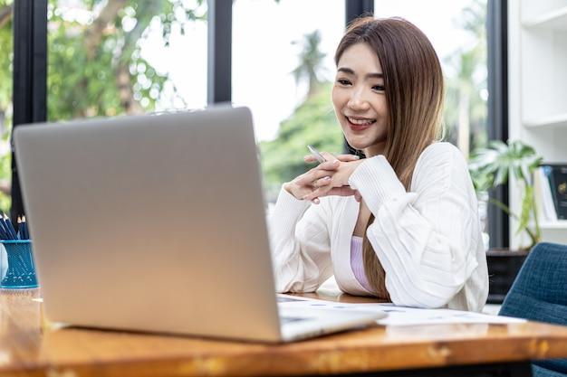 아름다운 아시아 여성 사업가가 개인 사무실에 앉아 노트북으로 영상 통화를 통해 파트너와 이야기하고 있으며 그녀는 신생 기업의 여성 임원입니다. 재무 관리의 개념