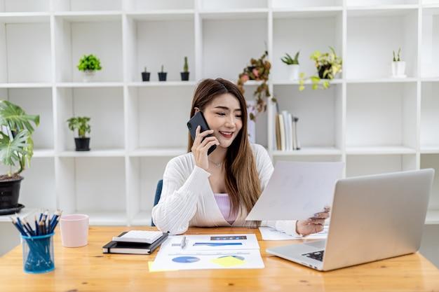 아름다운 아시아 여성 사업가가 방에 앉아 휴대폰으로 파트너와 통화하고 재무 문서를 확인하는 그녀는 신생 기업의 여성 임원입니다. 재무 관리.