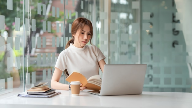 Beautiful asian businesswoman sitting at the office with a laptop and notebook.