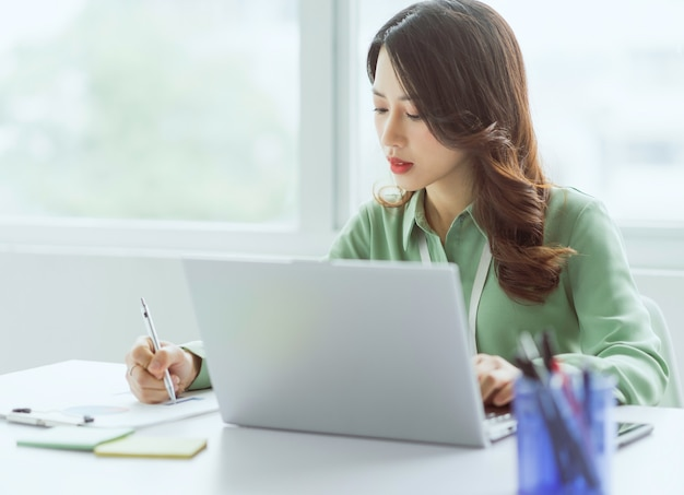 オフィスで働いて座っている美しいアジアの実業家