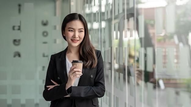 美しいアジアの実業家は、大きな鏡に寄りかかって、オフィスでコーヒーを持って立っています。