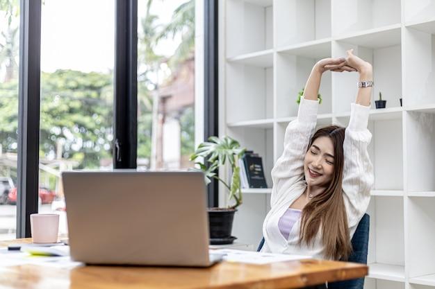 방에 서서 피곤할 때까지 오랜 시간 앉아 있다가 근육을 이완시키는 아름다운 아시아 여성 사업가입니다. 그녀는 스타트업 회사의 여성 임원입니다. 재무 관리 개념입니다.