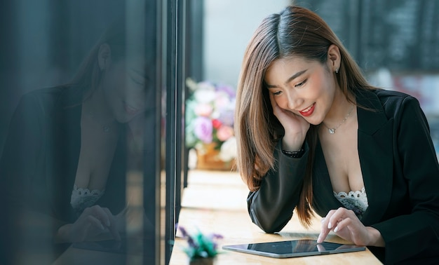幸せと共同ワークスペースで仕事の後にリラックスしながらタブレットを使用して美しいアジアの実業家。