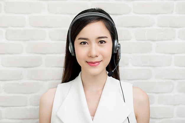 Beautiful asian businesswoman wearing microphone headset  as a telemarketing customer service agent