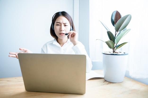 아름다운 아시아 콜센터 직원이 헤드폰과 마이크 케이블을 통해 고객에게 이야기하고 서비스를 제공합니다.