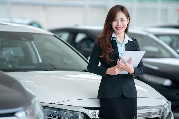 美しいアジアの自動車ディーラーは、ショールームで新車を販売し、車の販売を楽しんでいます。