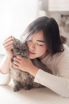 美しいアジアの猫の恋人の女性は彼女の部屋で猫と遊んでいます