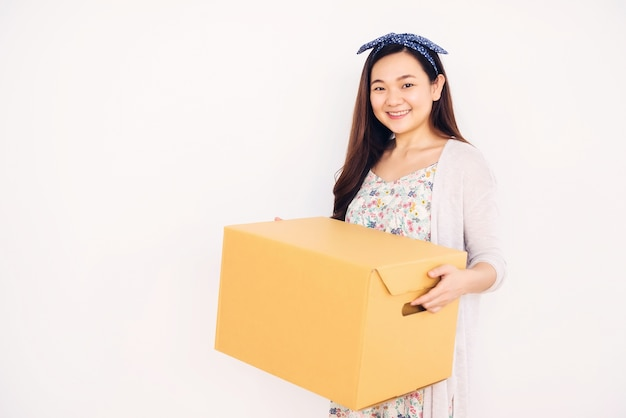 Beautiful asian chinese woman carrying cardboard box to move stuffs to new house