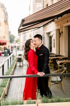 Beautiful asian couple holding hands and kissing in cafe in the old city
