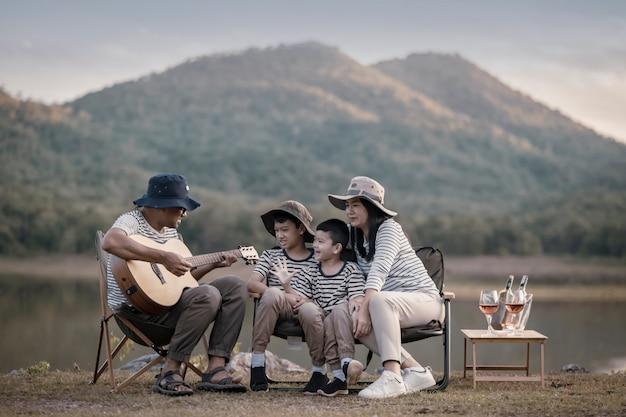호수와 산 근처 초원에서 피크닉을 하고 부활절 여름 파티를 하는 아름다운 아시아 가족. 휴일 및 휴가. 사람들의 생활 방식과 행복한 가족 생활 개념.