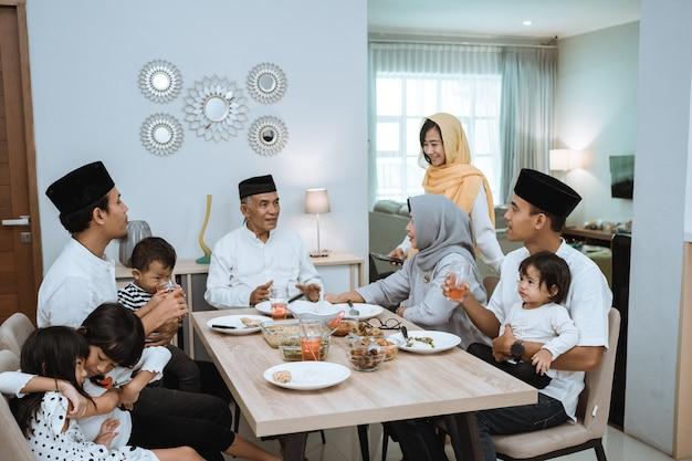 Красивая азиатская семья наслаждается ужином ифтар дома. рамадан карим ислам нарушает традицию поста