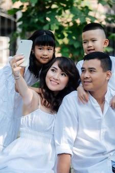 公園で自分撮りをしている白い服を着た美しいアジアの家族。彼らはピクニックをしていて、初秋の最後の暖かい日を楽しんでいます。木の影にいる親とその子供たち。