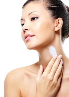 Bella femmina asiatica che applica crema idratante cosmetica sul collo