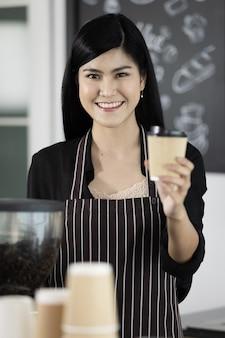 커피 기계 앞에 서있는 앞치마를 입고 아름 다운 아시아 여성 바리 스타. 그녀는 종이 커피 잔을 들고 자신감과 친절한 태도로 카메라를 바라보고 있습니다.