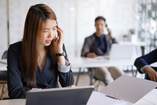 Beautiful asian female call center agent in headset consulting client.