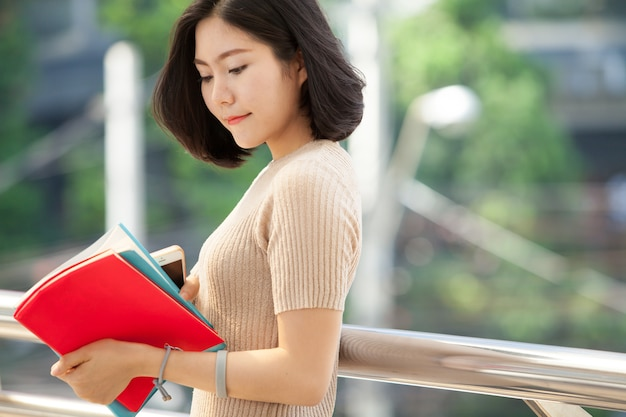 Beautiful asian female college student holding her books smiling happily