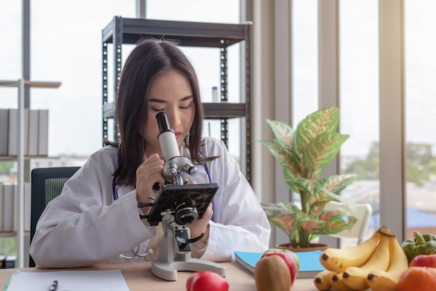 A beautiful asian female doctor looks at a microscope at a modern office desk with a large glass window background.
