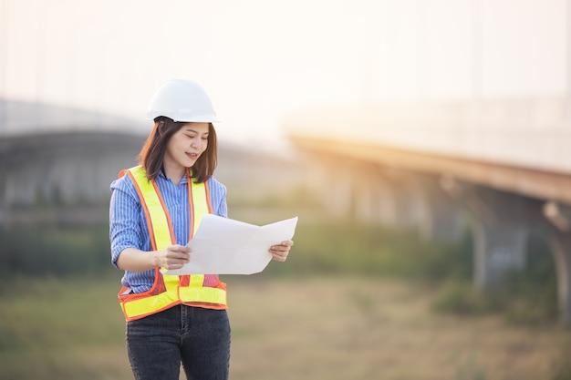 オフィスの外の建設現場で仕事をしている白い安全ヘルメットの美しいアジアの女性エンジニア。現代の働く女性の高速道路のアイデア