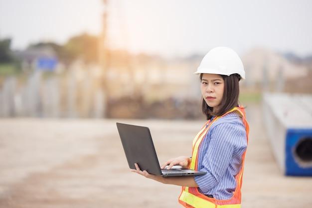 사무실 외부 건설 현장에서 일을 랩톱 컴퓨터 노트북을 사용하는 흰색 안전 하드 모자에 아름 다운 아시아 여성 엔지니어. 현대 일하는 여성을위한 아이디어.