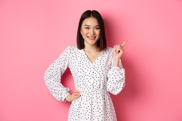 Bellissimo modello femminile asiatico sorridente, puntando il dito nell'angolo in alto a destra dello spazio della copia, mostrando banner pubblicitario, in piedi su sfondo rosa